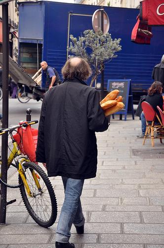 Man with Baguettes strolling through Paris